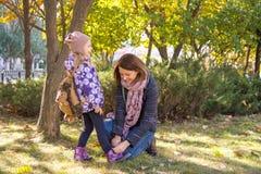 Mujer que ata a la hija de los jóvenes de los cordones Fotos de archivo