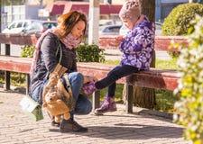 Mujer que ata a la hija de los jóvenes de los cordones Fotos de archivo libres de regalías