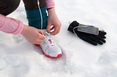 Mujer que ata las zapatillas deportivas en nieve Imagenes de archivo
