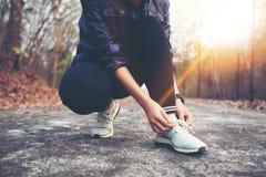 Mujer que ata los cordones de zapato para el corredor de la aptitud del deporte que consigue a las FO listas imagenes de archivo