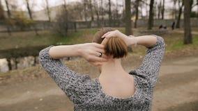 Mujer que ata su pelo liso en la cola de caballo, haciendo el peinado, visión trasera Concepto de Haircare almacen de video