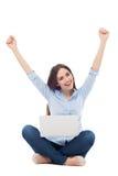 Mujer que aumenta los brazos delante de su ordenador portátil Fotos de archivo libres de regalías