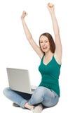 Mujer que aumenta sus brazos mientras que se sienta con la computadora portátil Foto de archivo