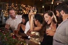 Mujer que aumenta un vidrio en una fiesta de Navidad en una barra