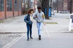 Mujer que ayuda al hombre ciego mientras que cruza el camino fotos de archivo
