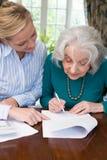 Mujer que ayuda al vecino mayor con papeleo Fotos de archivo libres de regalías