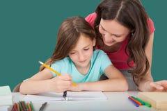 Mujer que ayuda a la hija en estudiar foto de archivo