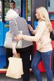 Mujer que ayuda a la mujer mayor a subir al autobús Fotografía de archivo