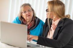 Mujer que ayuda a la señora adulta mayor en el ordenador portátil fotos de archivo