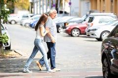 Mujer que ayuda a su padre While Crossing Road foto de archivo