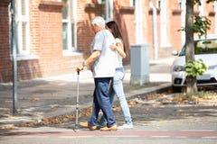 Mujer que ayuda a su padre While Crossing Road fotos de archivo