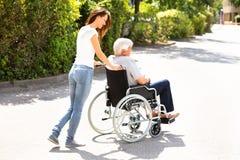 Mujer que ayuda a su padre discapacitado On Wheelchair imagen de archivo