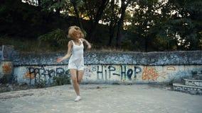 Mujer que baila coreografía moderna en parque de la ciudad, afuera Ruinas y pintada de la ciudad metrajes