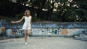 Mujer que baila coreografía moderna en parque de la ciudad, afuera Ruinas y pintada de la ciudad almacen de video