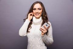 Mujer que baila a la música que escucha el teléfono con los auriculares Imágenes de archivo libres de regalías