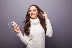 Mujer que baila a la música que escucha el teléfono con los auriculares Fotos de archivo libres de regalías