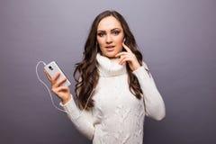Mujer que baila a la música que escucha el teléfono con los auriculares Foto de archivo