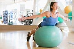 Mujer que balancea en bola suiza Imágenes de archivo libres de regalías