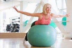 Mujer que balancea en bola suiza Foto de archivo libre de regalías