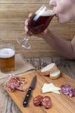 Mujer que bebe de un vidrio de cerveza Imagen de archivo libre de regalías