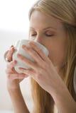 Mujer que bebe de una taza fotografía de archivo