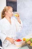 Mujer que bebe el jugo fresco en cocina Fotografía de archivo
