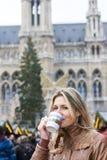 Mujer que bebe el vino caliente en el mercado de la Navidad Imágenes de archivo libres de regalías