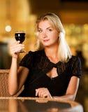 Mujer que bebe el vino rojo Fotografía de archivo