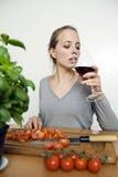 Mujer que bebe el vino rojo mientras que cocina Foto de archivo libre de regalías