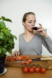 Mujer que bebe el vino rojo mientras que cocina Imágenes de archivo libres de regalías