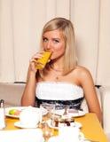 Mujer que bebe el zumo de naranja Imagen de archivo libre de regalías