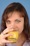 Mujer que bebe el zumo de naranja fotografía de archivo
