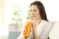 Mujer que bebe el zumo de naranja con una paja Fotografía de archivo