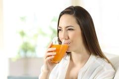 Mujer que bebe el zumo de naranja en un vidrio Fotos de archivo libres de regalías