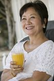 Mujer que bebe el zumo de naranja que sonríe al aire libre Fotografía de archivo