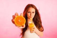 Mujer que bebe el zumo de naranja que sonríe mostrando naranjas Beaut joven Imágenes de archivo libres de regalías