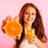 Mujer que bebe el zumo de naranja que sonríe mostrando naranjas Beaut joven Foto de archivo
