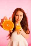 Mujer que bebe el zumo de naranja que sonríe mostrando naranjas Beaut joven Fotografía de archivo libre de regalías