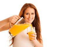 Mujer que bebe el zumo de naranja que sonríe mostrando naranjas Beaut joven Foto de archivo libre de regalías