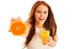 Mujer que bebe el zumo de naranja que sonríe mostrando naranjas Beaut joven Fotografía de archivo