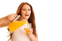 Mujer que bebe el zumo de naranja que sonríe mostrando naranjas Beaut joven Imagen de archivo
