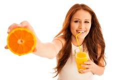 Mujer que bebe el zumo de naranja que sonríe mostrando naranjas Beaut joven Fotos de archivo libres de regalías