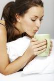 Mujer que bebe en cama Imagenes de archivo