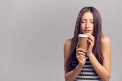 Mujer que bebe la bebida caliente de la taza de papel disponible Fotografía de archivo libre de regalías
