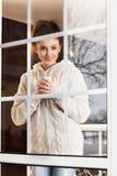 Mujer que bebe la bebida caliente que hace una pausa la ventana Imagen de archivo libre de regalías
