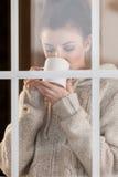 Mujer que bebe la bebida caliente que hace una pausa la ventana Foto de archivo libre de regalías
