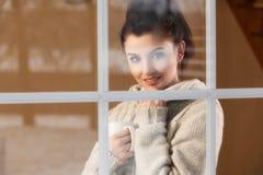 Mujer que bebe la bebida caliente que hace una pausa la ventana Fotos de archivo libres de regalías