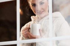 Mujer que bebe la bebida caliente que hace una pausa la ventana Fotografía de archivo libre de regalías