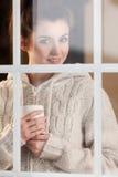 Mujer que bebe la bebida caliente que hace una pausa la ventana Foto de archivo