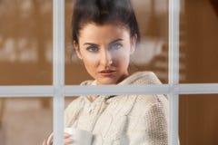 Mujer que bebe la bebida caliente que hace una pausa la ventana Imagenes de archivo